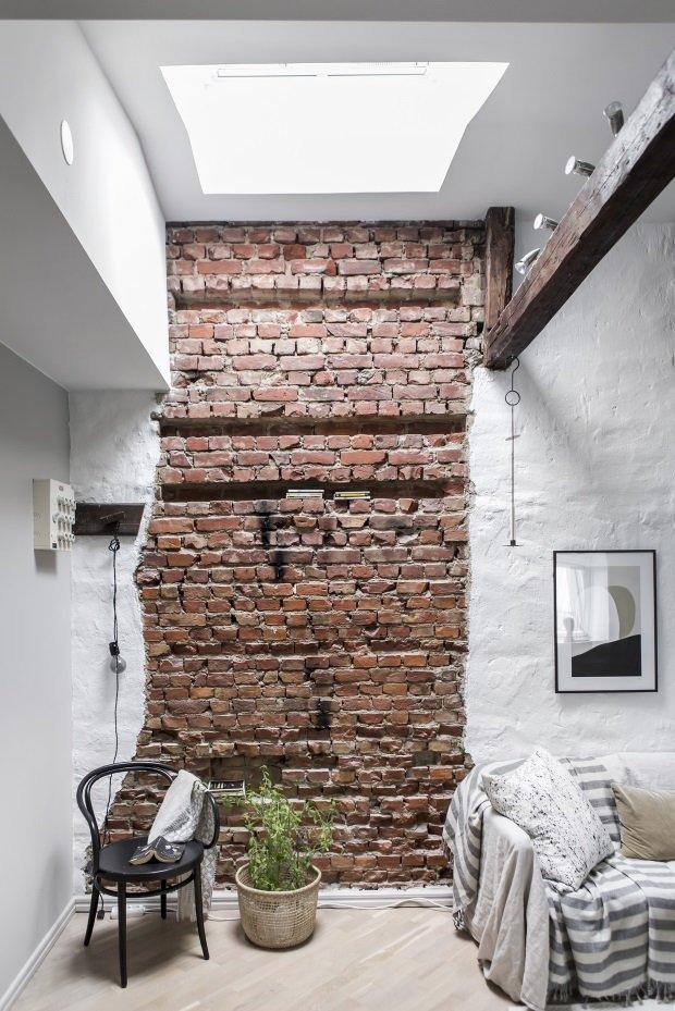 Кирпичная стена и окно в потолке в скандинавском лофте