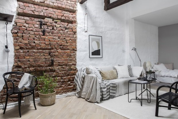 Кирпичная стена и балки на потолке в шведской квартире