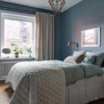 Спальня в скандинавском стиле: синие стены и золотистая каркасная люстра