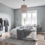 Спальня в скандинавском стиле: серые стены и вешалка на стене