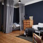 Спальня в скандинавском стиле: темно-синие стены в спальне и серые занавески, огораживающие кровать