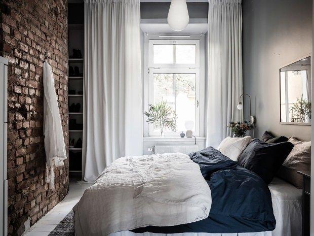 Спальня в скандинавском стиле: кирпичная стена в спальне напротив кровати