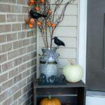 Ваза с тыквами и воронами у входной двери на Хэллоуин