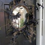 Зеркало с сухими ветками на двери на Хэллоуин