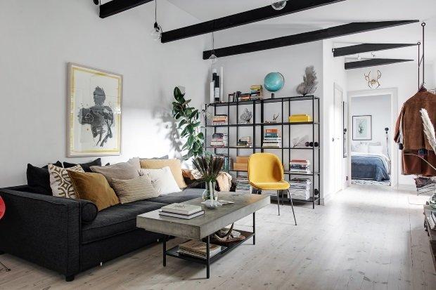Скандинавская квартира с яркими акцентами: серый диван с разноцветными подушками в гостиной