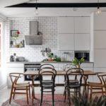 Скандинавская квартира с яркими акцентами: деревянный стол с разными стульями на кухне
