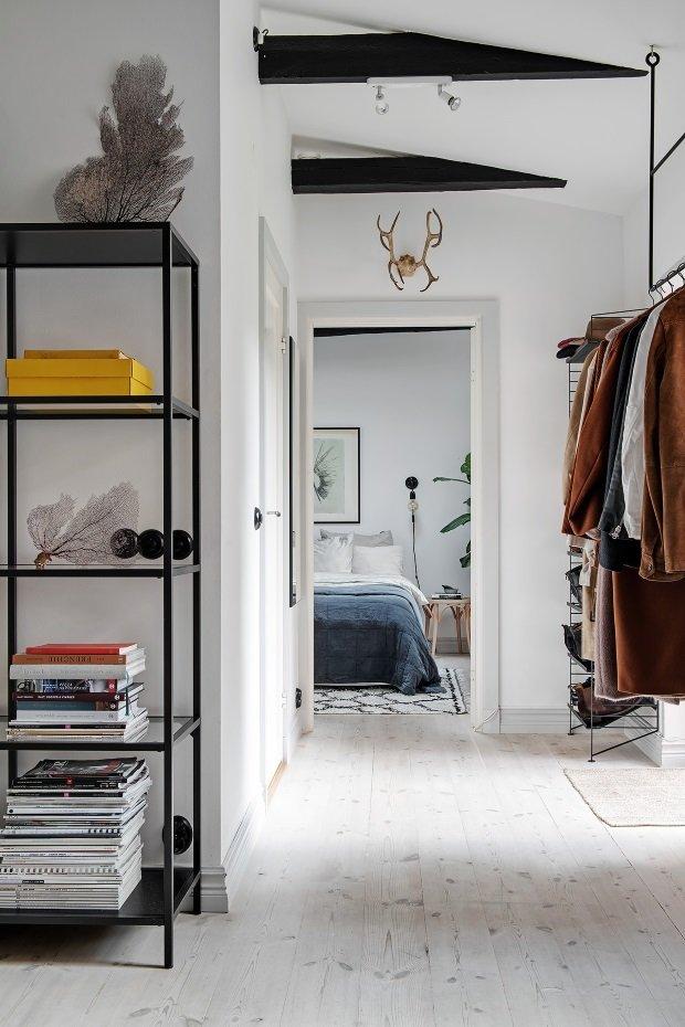 Скандинавская квартира с яркими акцентами: штанга для вешалок прикреплена к потолку