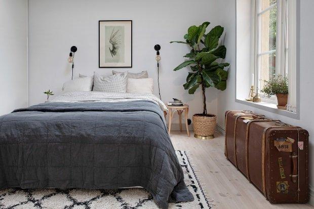 Скандинавская квартира с яркими акцентами: старинный чемодан в спальне