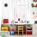Детская в скандинавском стиле: стол с яркой мебелью у окна